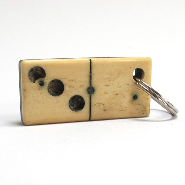 A vintage bone and wood domino keyring